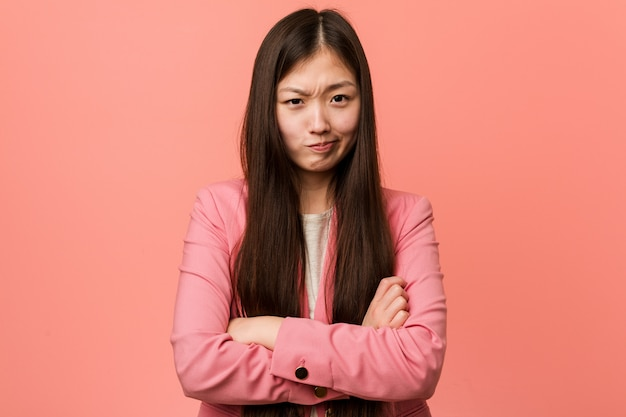 Young business chinese woman wearing pink suit frowning face in displeasure, keeps arms folded.