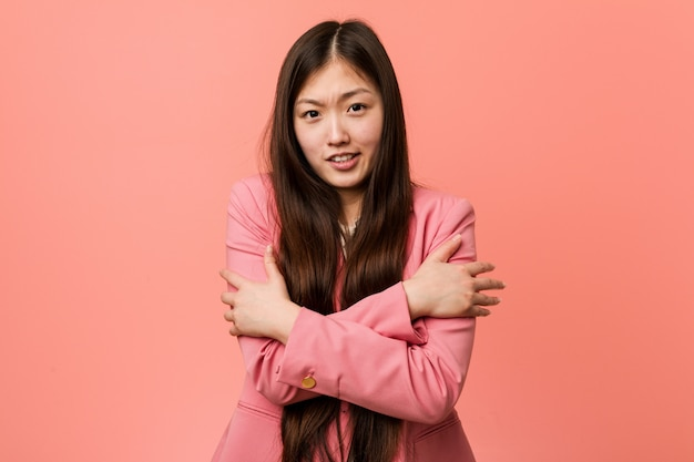 Young business chinese woman wearing pink suit going cold due to low temperature or a sickness.