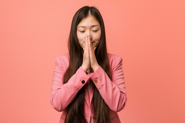 Young business chinese woman wearing pink suit holding hands in pray near mouth, feels confident.