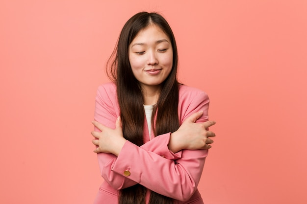 Young business chinese woman wearing pink suit hugs himself, smiling carefree and happy.
