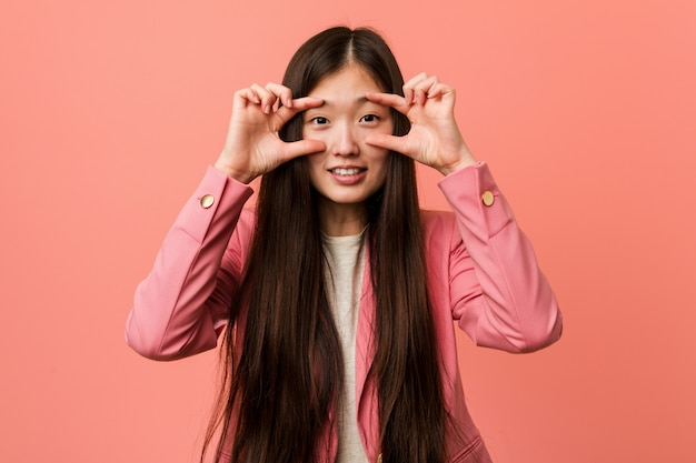 Young business chinese woman wearing pink suit keeping eyes opened to find a success opportunity.