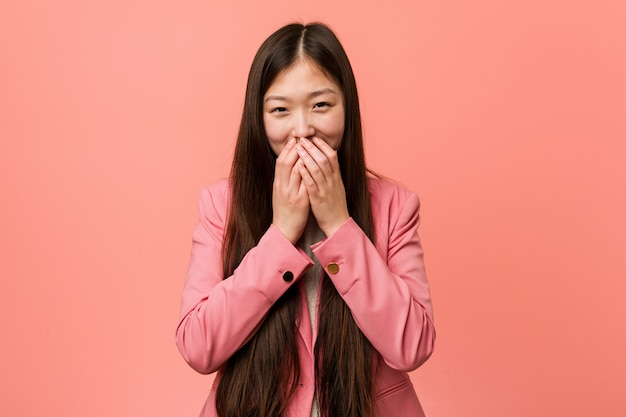 Young business chinese woman wearing pink suit laughing about something, covering mouth with hands.