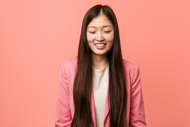 Young business chinese woman wearing pink suit laughs and closes eyes, feels relaxed and happy.