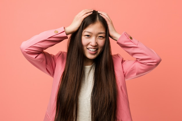 Young business chinese woman wearing pink suit laughs joyfully keeping hands on head. happiness concept.
