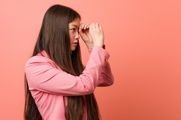 Young business chinese woman wearing pink suit looking far away keeping him hand on forehead.