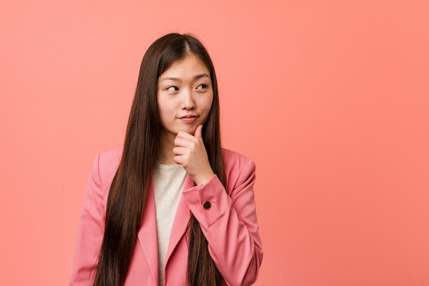 Young business chinese woman wearing pink suit looking sideways with doubtful and skeptical expression.