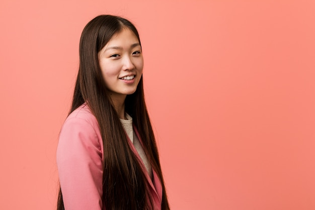 Young business chinese woman wearing pink suit looks aside smiling, cheerful and pleasant.