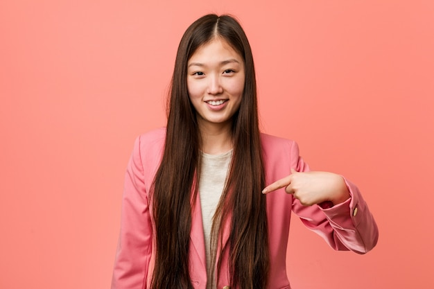 Young business chinese woman wearing pink suit person pointing by hand to a shirt blank space, proud and confident