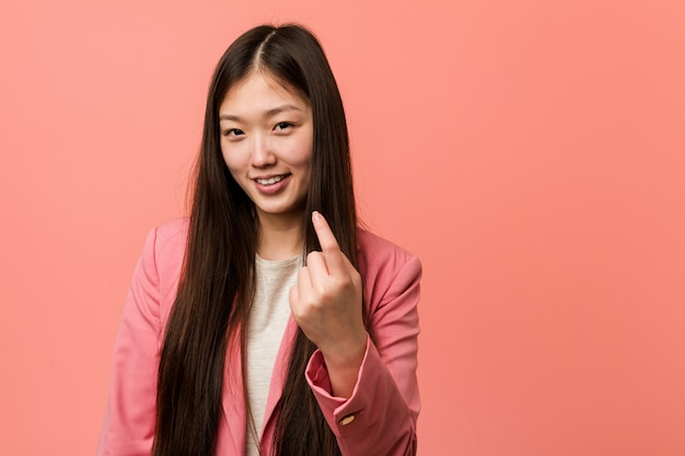 Young business chinese woman wearing pink suit pointing with finger at you as if inviting come closer.