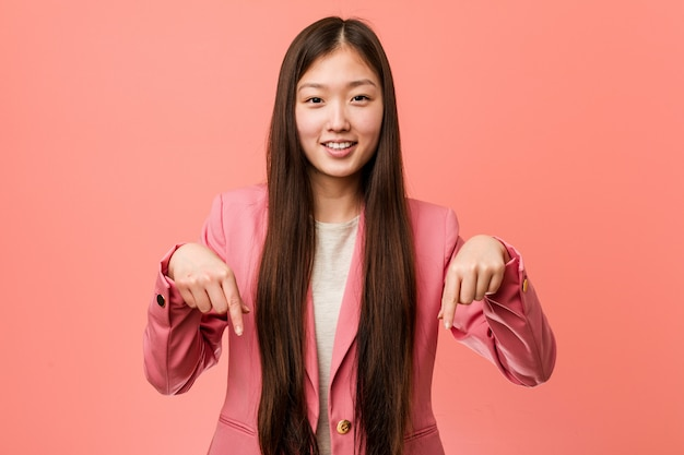 Young business chinese woman wearing pink suit points down with fingers, positive feeling.