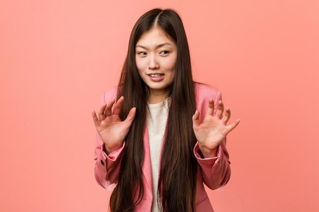 혐오의 제스처를 보여주는 누군가를 거부하는 분홍색 양복을 입고 젊은 비즈니스 중국 여자.