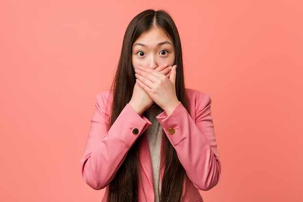 Young business chinese woman wearing pink suit shocked covering mouth with hands.