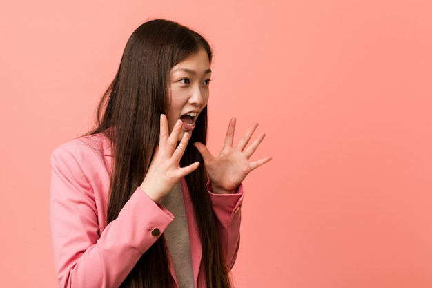 Young business chinese woman wearing pink suit shouts loud, keeps eyes opened and hands tense.