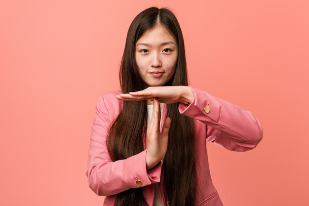 타임 아웃 제스처를 보여주는 분홍색 양복을 입고 젊은 비즈니스 중국 여자.