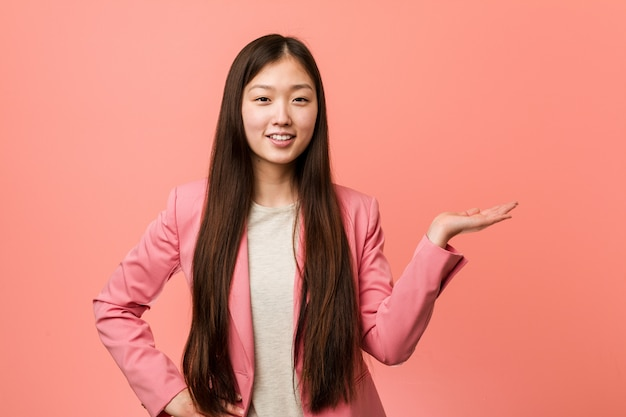 Young business chinese woman wearing pink suit showing a copy space on a palm and holding another hand on waist.