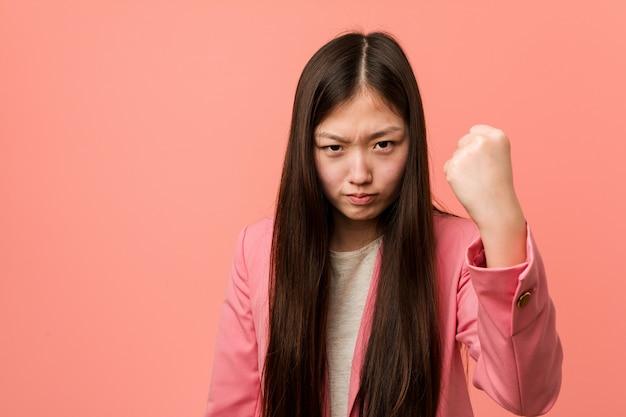 Женщина молодого дела китайская нося розовый костюм показывая кулак к камере, агрессивное выражение лица.