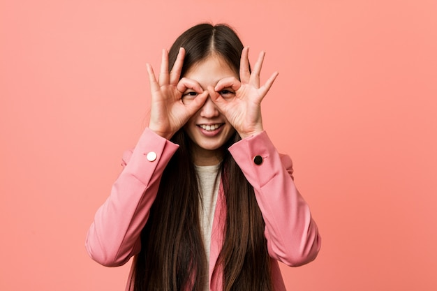 Young business chinese woman wearing pink suit showing okay sign over eyes
