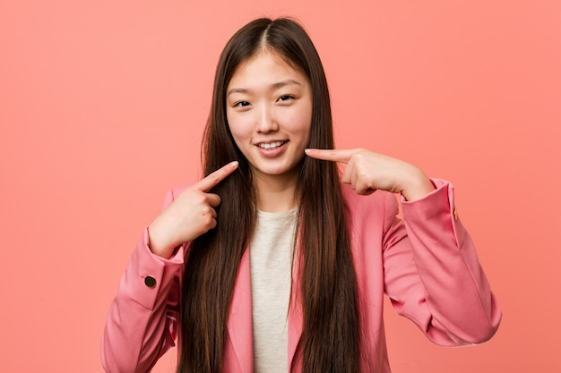 Young business chinese woman wearing pink suit smiles, pointing fingers at mouth.
