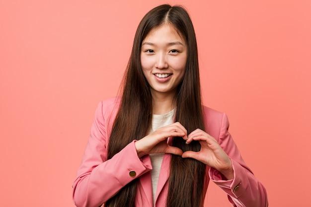 ピンクのスーツを着て笑顔で彼の手でハートの形を示している若いビジネス中国人女性。