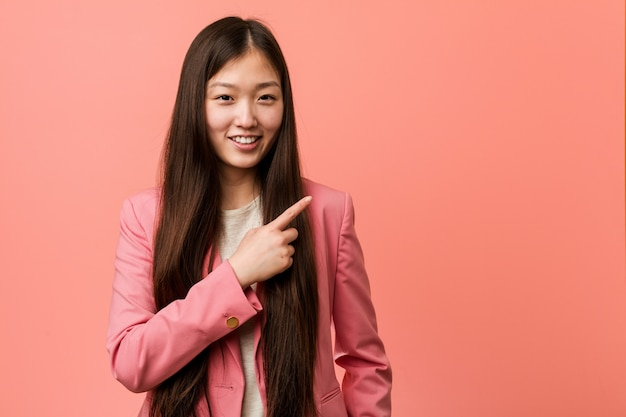 Young business chinese woman wearing pink suit smiling and pointing aside, showing something at blank space.