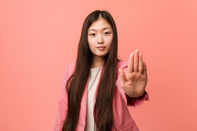 정지 신호를 보여주는 뻗은 손으로 서 분홍색 양복을 입고 젊은 비즈니스 중국 여자는 당신을 방지합니다.
