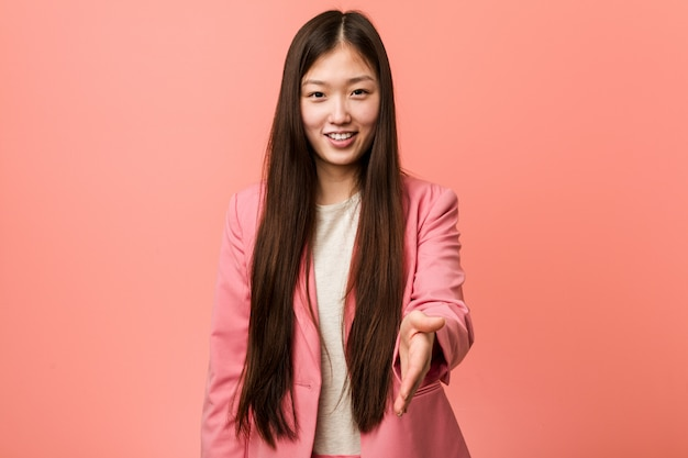 Young business chinese woman wearing pink suit stretching hand at camera in greeting gesture.