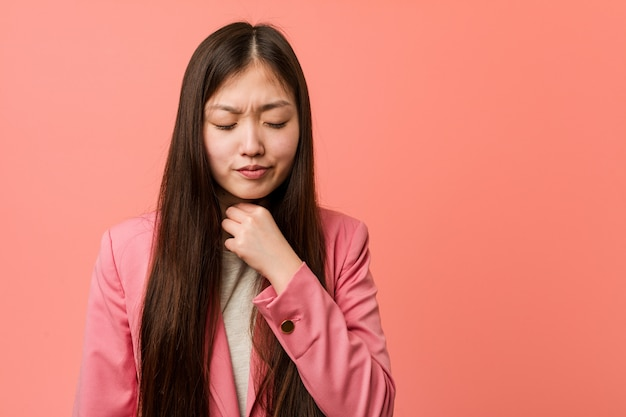 Young business chinese woman wearing pink suit suffers pain in throat due a virus or infection.