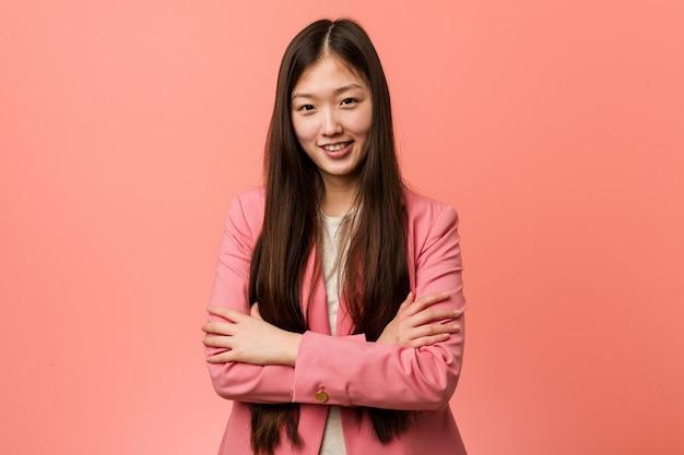 Молодая деловая китаянка в розовом костюме, которая чувствует себя уверенно, решительно скрестив руки.