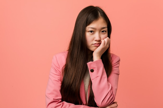 Young business chinese woman wearing pink suit who is bored, fatigued and need a relax day.