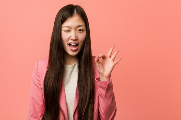 Young business chinese woman wearing pink suit winks an eye and holds an okay gesture with hand.
