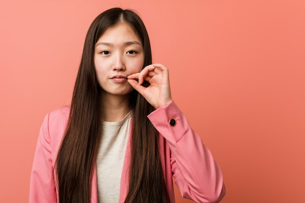 Young business chinese woman wearing pink suit with fingers on lips keeping a secret.
