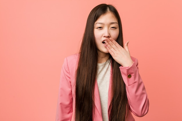 Young business chinese woman wearing pink suit yawning showing a tired gesture covering mouth with him hand.