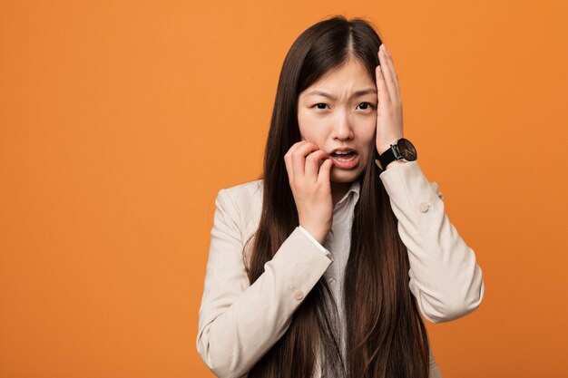 Young business chinese woman whining and crying disconsolately.