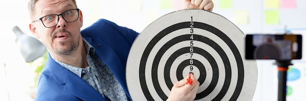 Young business coach hitting target in front of the mobile phone camera goal of successful
