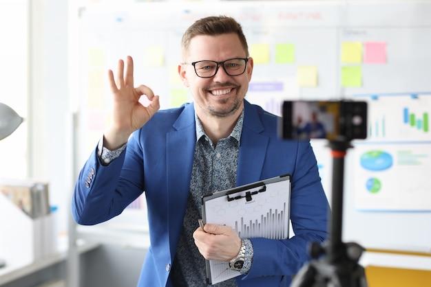 Молодой бизнес-тренер показывает жест ок перед камерой мобильного телефона