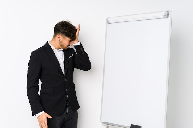 Young business coaching arabian man forgetting something, slapping forehead with palm and closing eyes.