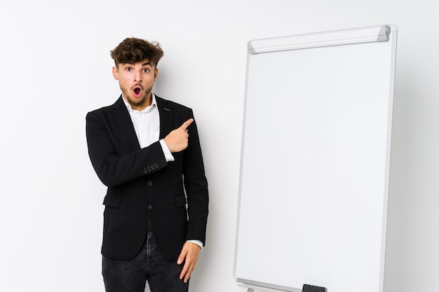 Young business coaching arabian man pointing to the side