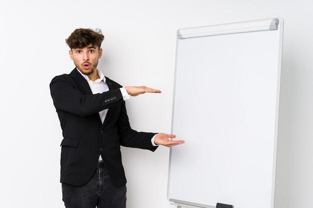 Молодой бизнес тренер аравийский человек шокирован и поражен, удерживая копию пространство между руками.