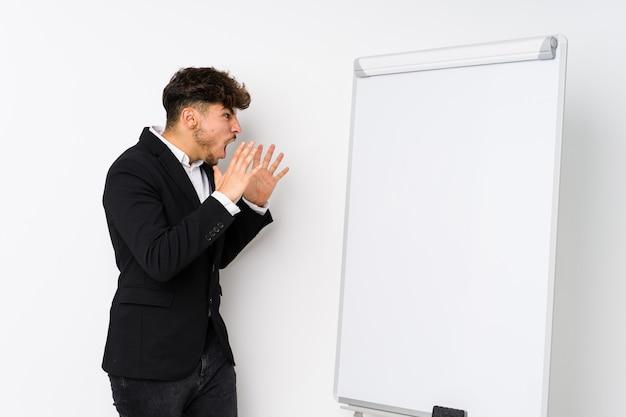 Young business coaching arabian man shouts loud, keeps eyes opened and hands tense.