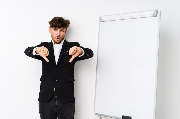 Молодой арабский человек, тренирующий бизнес, показывает палец вниз и выражает неприязнь.