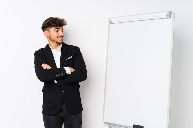 Молодой бизнес коучинг арабский мужчина уверенно улыбается со скрещенными руками.