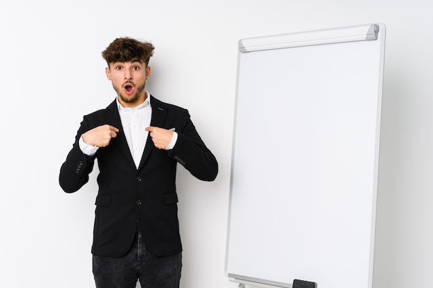 Young business coaching arabian man surprised pointing with finger, smiling broadly.