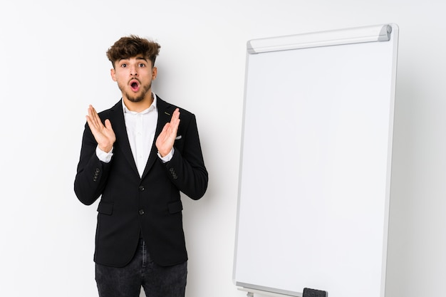 Young business coaching arabian man surprised and shocked.