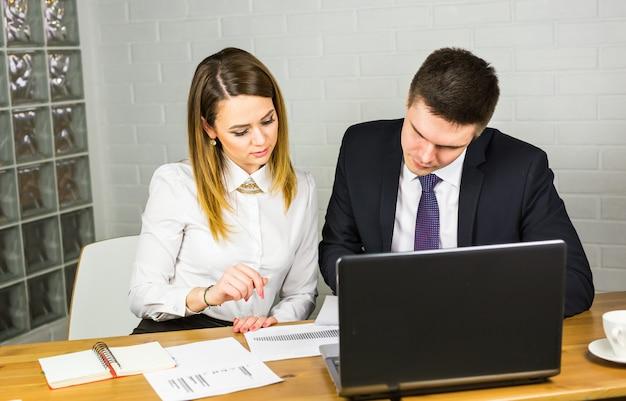 Молодые коллеги по бизнесу обсуждают работу на портативном компьютере в пространстве совместной работы, корпоративных бизнесменов