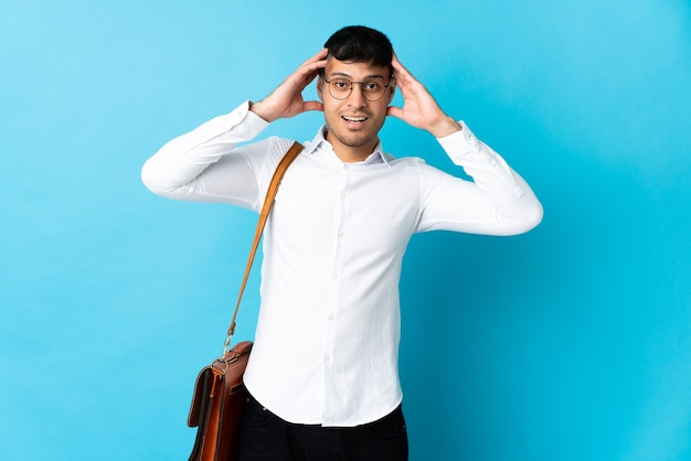 Young business colombian man isolated on blue with surprise expression