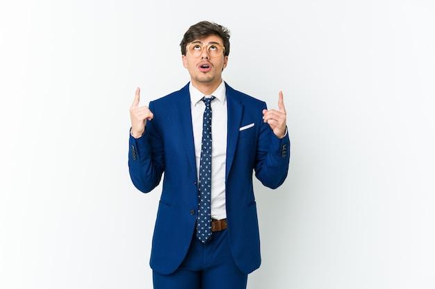 口を開けて逆さまを指している若いビジネスクールな男。