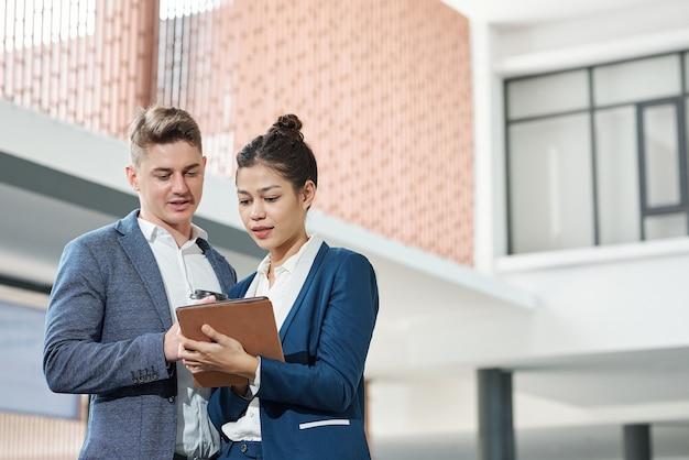 Молодая деловая пара обсуждает информацию на экране планшетного компьютера