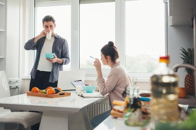 Молодая деловая пара на кухне пьет и ест во время работы над электронными устройствами