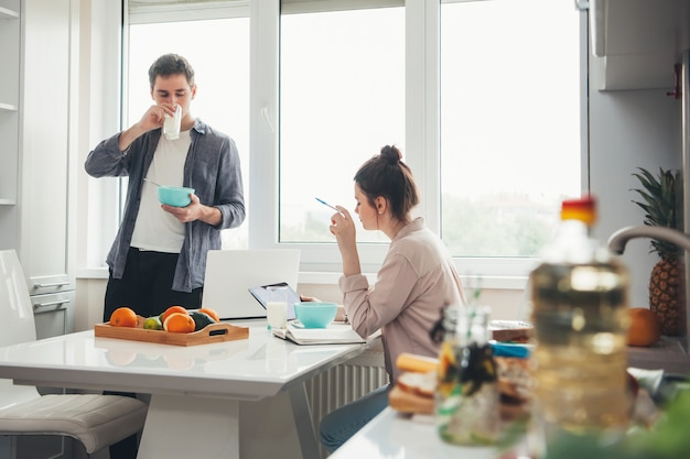 Young business couple in the kitchen drinking and eating while working on electronic devices