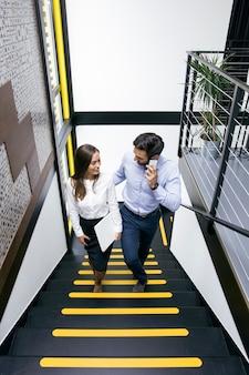 Молодая деловая пара на лестнице в офисе